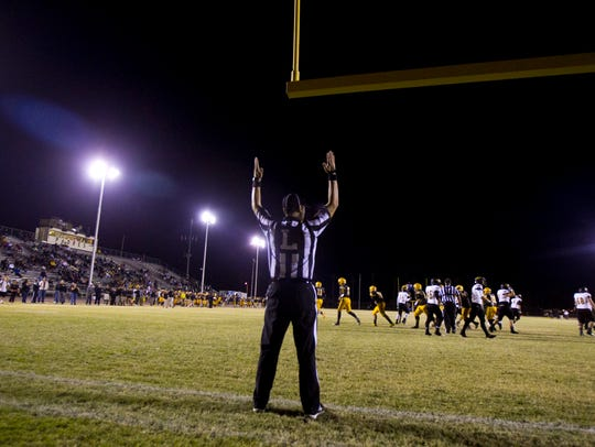 A line judge signals a field goal good during a high