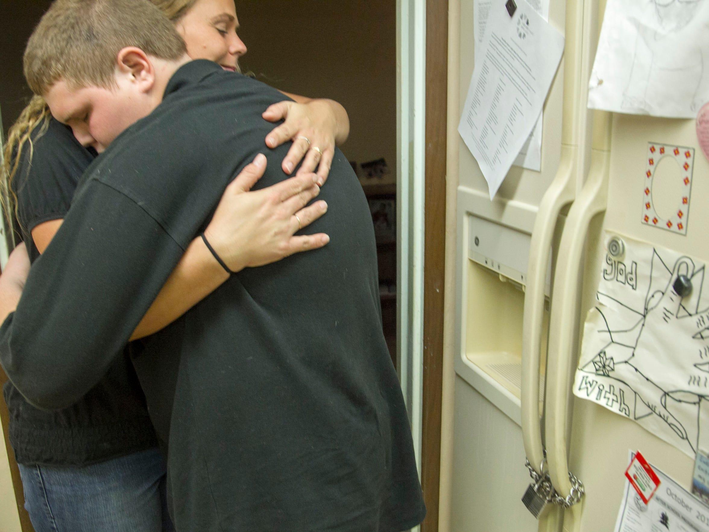 Misty Kidder, a Phoenix mother, hugs her son Austin