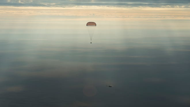 In this photo released by NASA,  the Soyuz MS-01 spacecraft descends beneath a parachute with NASA astronaut Kate Rubins, Russian cosmonaut Anatoly Ivanishin of Roscosmos, and astronaut Takuya Onishi of the Japan Aerospace Exploration Agency (JAXA) near the town of Zhezkazgan, Kazakhstan Sunday, Oct. 30, 2016. A Russian Soyuz space capsule has landed in Kazakhstan, bringing back three astronauts from the United States, Japan and Russia back to Earth from a 115-day mission aboard the International Space Station.