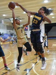 Tiyan Titans' Jaeda James is forced to alter her shot under the towering defense of Guam High Panthers' Britney Bailey in an Independent Interscholastic Athletic Association of Guam Girls' Basketball League game at George Washington High School on Dec. 9.