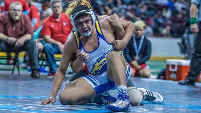 Kirtland Central's Cody Manuelito looks for an escape against Albuquerque Academy's Mitchell Nunez during the 182-pound third-place match on Saturday at the Santa Ana Star Center in Rio Rancho.