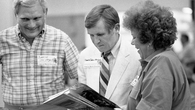 Tennessee Vols head football coach Johnny Majors, center, signs a brochure for former state Sen. Joe Haynes, left, and Judge Barbara Haynes during UT Alumni picnic at the Tennessee State Fairgrounds July 23, 1985.
