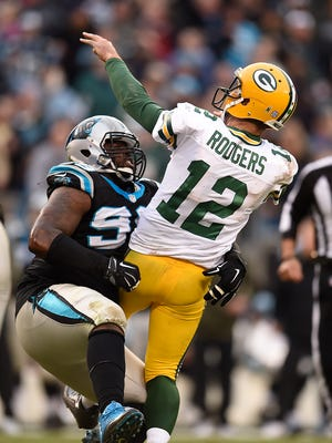 Green Bay Packers quarterback Aaron Rodgers gets hit by Carolina Panthers Kawann Short (99) late in the fourth quarter during Sunday's game at Bank of America Stadium in Charlotte, NC. Rodgers threw an interception on the play. The Panthers went on to defeat the Packers 37-29.