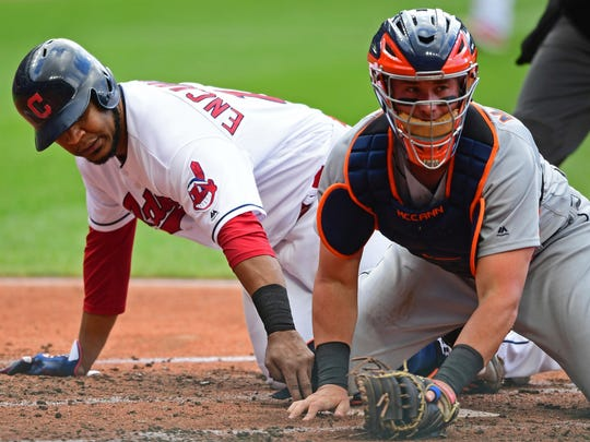 Cleveland Indians' Edwin Encarnacion, left, touches home plate as Detroit Tigers catcher James McCann looks for the ball the first inning Saturday, June 23, 2018, in Cleveland. Encarnacion scored on a single by Brandon Guyer and error by McCann.