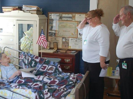 Hospice staff and volunteer salute a veteran.