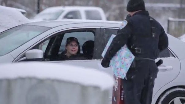 Lowell police officer Scott VanSolkema hands out presents to drivers.