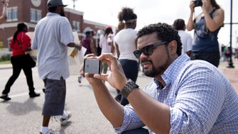 St. Louis Alderman Antonio French, 21st Ward, photographs protesters in Ferguson, Mo., Aug. 11, 2014. French helped sponsor a bill to establish a civilian police review board.