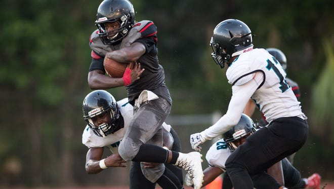 South Fork's R.J. Weaver runs for a first down during the team's first drive of the game in the first quarter against Royal Palm Beach during the Kickoff Classic high school football game Friday, Aug. 18, 2017, at South Fork High School in Tropical Farms. Royal Palm Beach's Curtis Bunche Jr. wraps Weaver up from underneath to end the play.