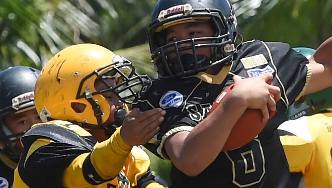 Eagles player Ethan-Chris Tedtaotao (27) applies defensive pressure on the Saints' Dylan Peter Manibusan (6) during their Triple J Ford GNYFF Youth Football League game at Eagle Field in Mangilao on Aug. 30.