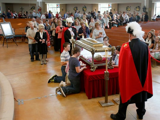 A long line of people wait their turn to view the relics of St. Maria Goretti, a Catholic saint,  at Our Lady of Good Counsel parish on Thursday, Oct. 8, 2015, in Plymouth.