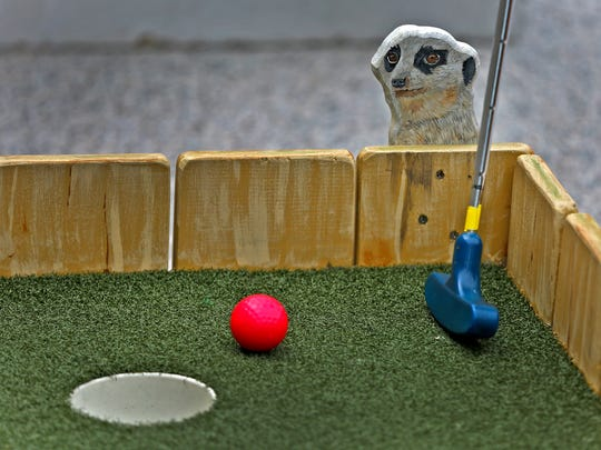 A meerkat figure peeks at the ball in the Putting Around Africa hole in the Alliance Sculpture Garden at Mini Golf at the IMA, Tuesday, May 23, 2017.