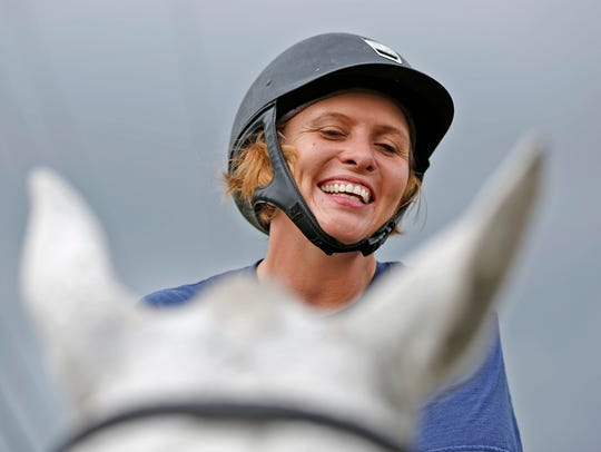 Lorie Phillips smiles as she rides Stretch, during