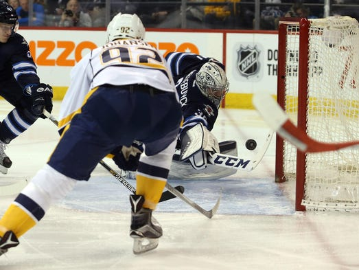 Jets goalie Connor Hellebuyck (30) looks for a loose