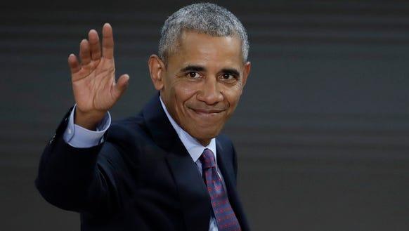Former president Barack Obama waves as he leaves the