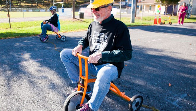 Dave Shue, a board member of Community Child Care, laughs while competing in a tricycle relay race as part of a fundraiser for the organization in Staunton on Saturday, Oct. 17, 2015.