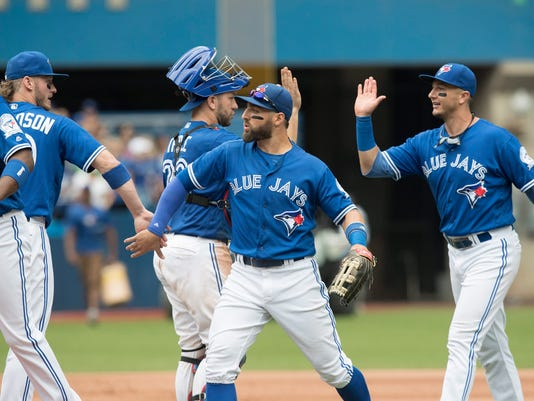 Toronto Blue Jays' Troy Tulowitzki,Kevin Pillar, Josh Thole and Josh Donaldson, from right to left, celebrate after the Mariners defeated the Seattle Mariners 2-0 in a baseball game in Toronto on Sunday July 24, 2016. (Fred Thornhill/The Canadian Press via AP)
