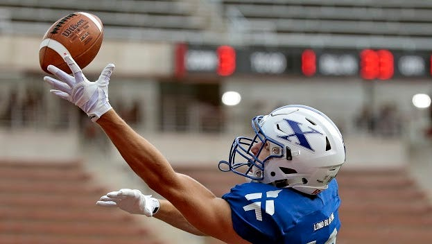 St. Xavier receiver Colton Paul (10) reaches for a pass in the end zone but back catch up to it during the first quarter of the Crosstown Showdown high school football game between St. Xavier and Covington Catholic at Nippert Stadium on the University of Cincinnati campus in Cincinnati, Ohio, on Friday, Aug. 28, 2015. St. Xavier allowed just one touchdown in its 57-7 win over Covington Catholic.