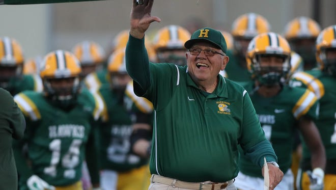 Farmington Hills Harrison coach John Herrington leads his team onto the field before Harrison's 39-0 win over Berkley, allowing Herrington to set the record for most wins in state history on Friday, Oct. 13, 2017, at Harrison.