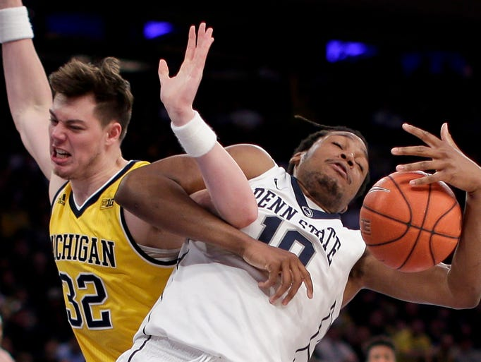 Michigan forward Ricky Doyle (32) gets tangled up with