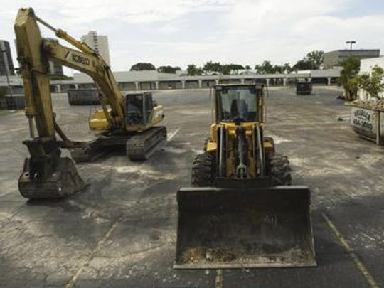 Construction equipment and Dumpsters sit in a mostly empty parking lot in August 2003 before the demolition of Edison Ford Square.