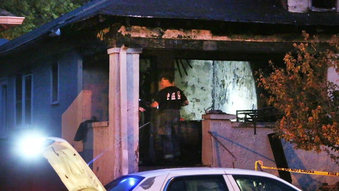 Crime scene investigators look around inside a house in the 3600 block of East New York Street early Thursday morning, Oct. 22, 2015. Indianapolis Fire Department crews were called to the duplex shortly before 3:20 a.m. One man was rescued and taken to Eskenazi Hospital in extremely critical condition.