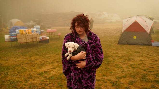 "Shayanne Summers holds her dog Toph while wrapped in a blanket after several days of staying in a tent at an evacuation center at the Milwaukie-Portland Elks Lodge, Sunday, Sept. 13, 2020, in Oak Grove, Ore. ""It's nice enough here you could almost think of this as camping and forget everything else, almost,"" said Summers about staying at the center after evacuating from near Molalla, Oregon which was threatened by the Riverside Fire."