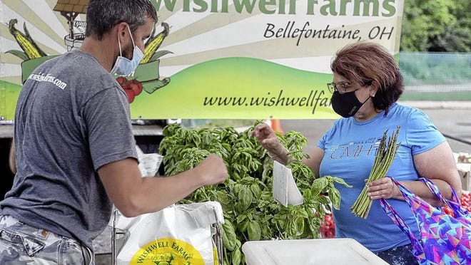 Jason Wish, owner of Wishwell Farms, helps Andrea Tippery of Reynoldsburg browse produce during the first Reynoldsburg Farmers Market of the season at John F. Kennedy Park, 7232 E. Main St.