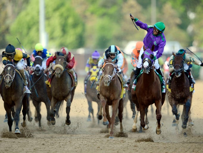Victor Espinoza aboard California Chrome (in purple) celebrates after winning the 2014 Kentucky Derby.