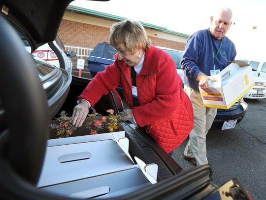 Adena Hospice volunteers Carolyn Schneider and Chip Walder load two vehicles with decorative handmade vases and flowers Tuesday for delivery. The hospice will deliver 26 meals, featuring ham or turkey and including enough to feed six to eight people, in two days.