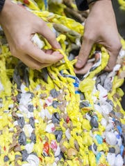 Emily Dorrell weaves braided strands of plastic bags into a sleeping mat at Newark Charter.