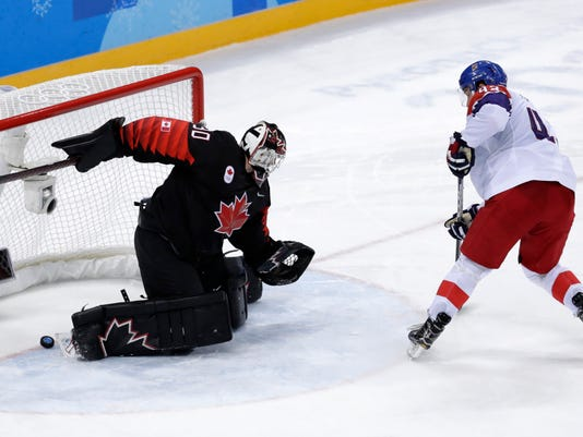 Jan Kovar (43), of the Czech Republic, scores past goalie Ben Scrivens (30), of Canada, in the penalty shootout during the overtime period of the preliminary round of the men's hockey game at the 2018 Winter Olympics in Gangneung, South Korea, Saturday, Feb. 17, 2018. (AP Photo/Julio Cortez)