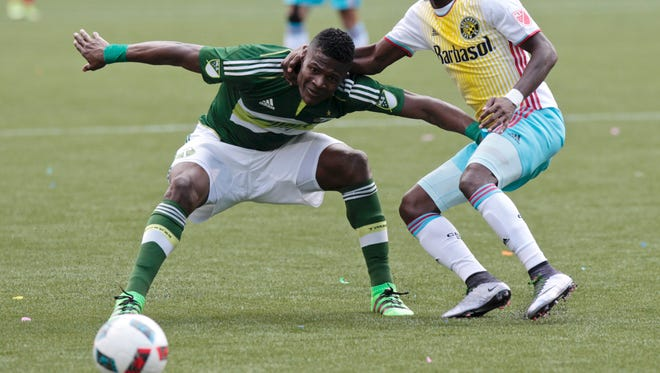 Portland Timbers forward Dairon Asprilla, left, and Columbus Crew defender Harrison Afful, right, battle for the ball during the second half of an MLS soccer match in Portland, Ore., Sunday, March 6, 2016. The Portland Timbers won 2-1.