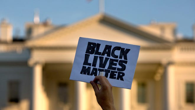 "A man holds up a sign saying ""black lives matter"" during a protest of shootings by police, at the White House."