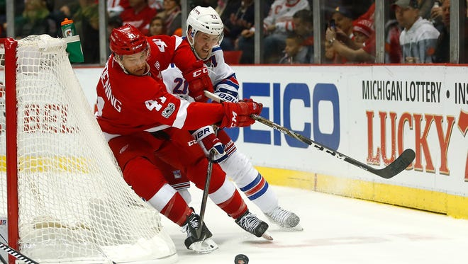 Luke Glendening of the Detroit Red Wings tries to get around the stick of  Derek Stepan of the New York Rangers during the second period Sunday.