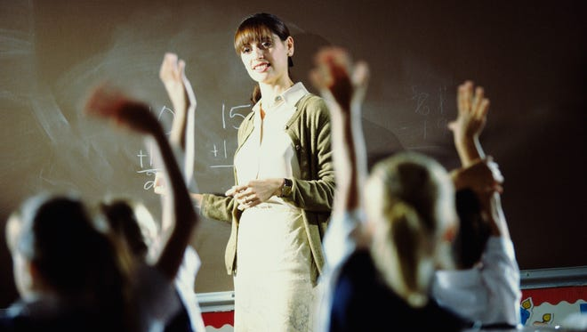 A teacher leads a class to young students.