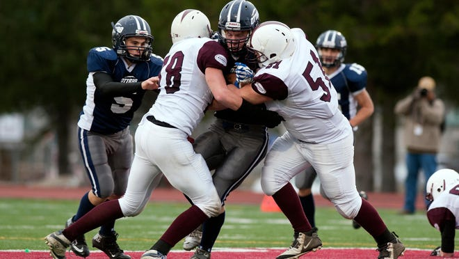 Otter Valley's Carson Leary is wrapped up by BFA-Fairfax's Kyle Combs, right, and David Legris, left, in last year's Division III high school football state championship game. Leary and Legris are back for their respective teams.