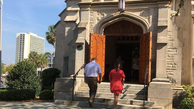 Congregation members of St. John's Cathedral in downtown Jacksonville arrive for Sunday morning worship despite concerns about the coronavirus pandemic. The closeknit church, however, took precautions to prevent the spread of the deadly virus including hand sanitizers throughout the cathedral, social distancing between seats in the pews and perhaps, hardest of all, no hugging or handshakes.