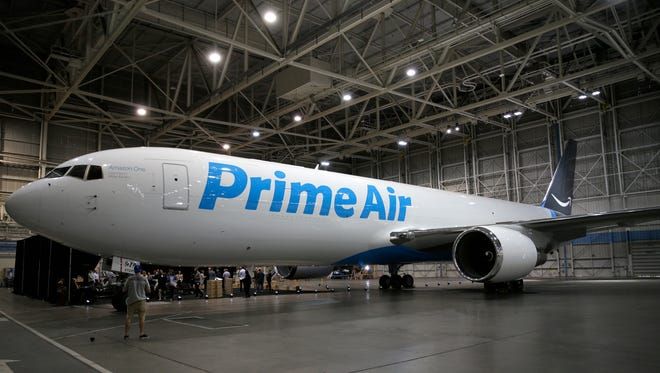 """A Boeing 767, an Amazon.com """"Prime Air"""" cargo plane is parked on display Thursday, Aug. 4, 2016, in a Boeing hangar in Seattle. Amazon unveiled its first branded cargo plane Thursday, one of 40 jetliners that will make up Amazon's own air transportation network of 40 Boeing jets leased from Atlas Air Worldwide Holdings and Air Transport Services Group Inc., which will operate the air cargo network. (AP Photo/Ted S. Warren)"""