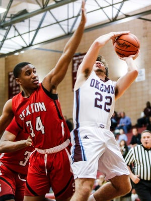 Okemos senior Luke Stagg connects from the paint against Sexton's Karl Brooks Tuesday, Jan. 10, 2017, at Okemos.