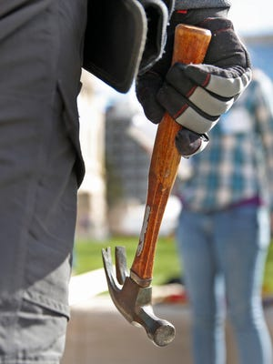 Speaker of the House Brian Bosma, hammer in hand, pauses as he joins other Indiana lawmakers and volunteers at the General Assembly's first-ever Habitat for Humanity build at the Statehouse, Wednesday, March 8, 2017.