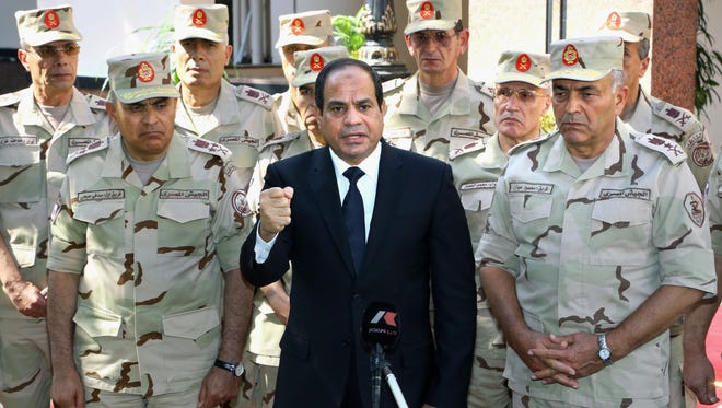 In this Oct. 25, 2014 file photo provided by Egypt's state news agency MENA, Egyptian President Abdel-Fattah el-Sissi, center, speaks on state-run TV ahead of a military funeral for troops killed in an assault in the Sinai Peninsula, in Cairo, Egypt.