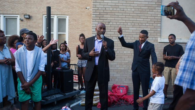 Head of Thomas Edison Charter School Salome Thomas-EL is applauded by staff, parents and members of the community during a protest-turned-celebration Monday for the educator.