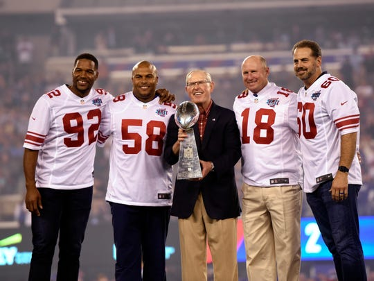 (L-R) From the 2007 Super Bowl XLII winning team, Michael Strahan, Antonio Pierce, head coach Tom Coughlin, Jeff Feagles, and Shaun O'Hara stand on the stage during the ceremony. New York Giants against the Detroit Lions in their home opener on Monday, September 18, 2017 in East Rutherford.