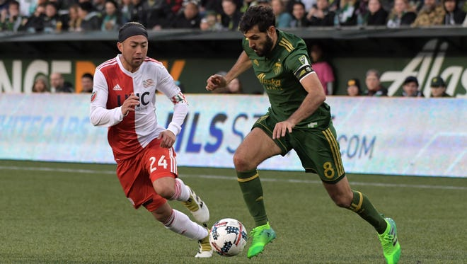 Apr 2, 2017; Portland, OR, USA; Portland Timbers midfielder Diego Valeri (8) is defended by New England Revolution midfielder Lee Nguyen (24) during a MLS soccer match at Providence Park.
