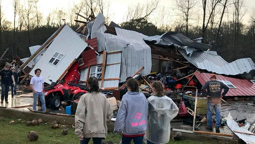 People examine a barn owned by the Miller family that was destroyed during a storm south of Mount Olive, Miss., Monday, Jan. 2, 2017. Forecasters say damaging winds, hail and flash flooding will be possible on Monday as a storm system moves across the South.