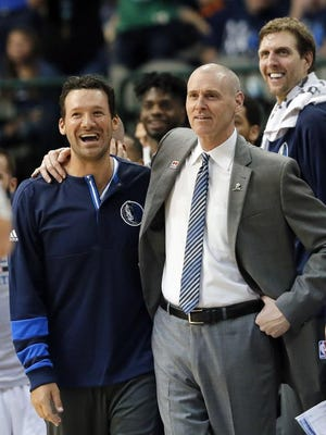 Former Dallas Cowboys quarterback Tony Romo stands by the bench with Dallas Mavericks head coach Rick Carlisle and Dirk Nowitzki, rear, of Germany in the final minutes of the second half of an NBA basketball game against the Denver Nuggets in Dallas, Tuesday, April 11, 2017. (AP Photo/Tony Gutierrez)