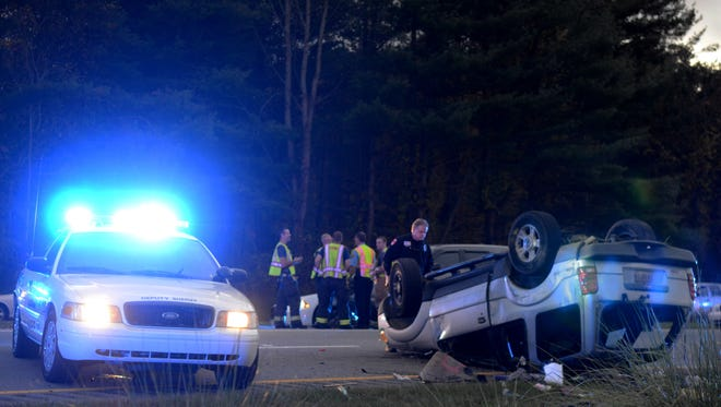 Police officers inspect the SUV that flipped over on I-240 near Exit 8 Tuesday, ending a chase by the Buncombe County Sheriff's Office.
