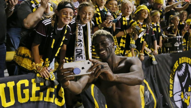 Crew forward Gyasi Zardes takes photos with fans after a match against Philadelphia last September. The team announced on Monday that it will play at home Thursday without fans in attendance.