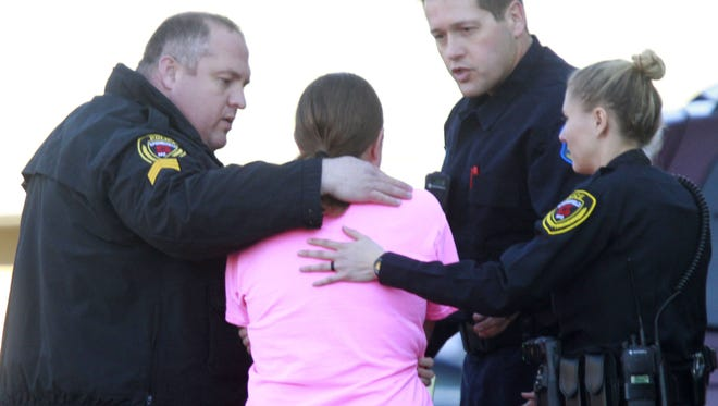 Springfield police officers comfort a woman believed to be the mother of two children who were killed at the Lake Shore Apartments in south Springfield in March. There were 13 homicides in the city of Springfield in 2015.