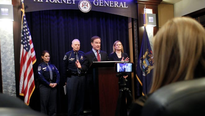Michigan Attorney General Bill Schuette announces 22 new charges against Larry Nassar Feb. 22, 2017, in the Attorney General's office.  Flanking the AG are (from l.) MSU Police Chief and Director Jim Dunlap, and Assistant Prosecuting Attorney Angela Povilaitis.